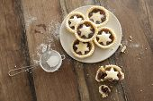 picture of icing  - Overhead view of a plate of decorative freshly baked Christmas mince pies with pastry stars alongside a half eaten pie and strainer with icing sugar to dust the top - JPG