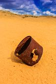 broken rusty can on sand in desert