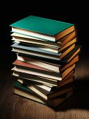 Stack of hardcover books arranged haphazardly viewed from a high angle on a wooden desk or table wit