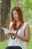 Beautiful young redhead Asian woman reading a book