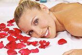 Smiling young woman laying in health resort spa with rose petals