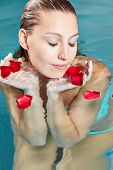 Young woman bathing with red rose petals in swimming pool