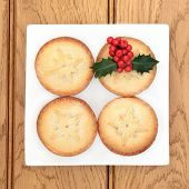 Christmas mince pie cakes and holly on a plate over oak background.