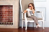 Little girl is sitting on the chair