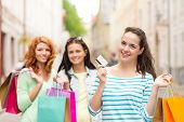 tourism, travel, vacation, shopping and friendship concept - smiling teenage girls with shopping bag