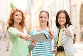 tourism, travel, leisure, holidays and friendship concept - smiling teenage girls with tablet pc com