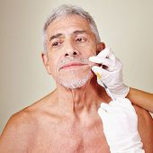 Old man getting wrinkle treatment with hyaluronic acid in beauty parlor