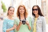 tourism, travel, leisure, holidays and friendship concept - smiling teenage girls with camera outdoo