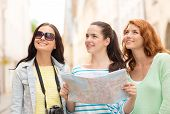 tourism, travel, leisure, holidays and friendship concept - smiling teenage girls with map and camer