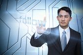 Businessman pointing to word follow against circuit board on futuristic background