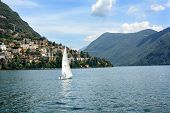 LUGANO, SWITZERLAND - JULY 5, 2014: Sailboat on Lake Lugano, with Mt. Bre and Castagnola in the back