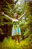 Young woman standing with arms outstretched in field against the trees