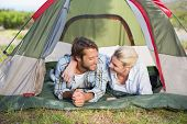 Attractive couple lying in their tent smiling at each other on a sunny day