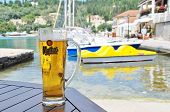 PAXOS, GREECE - JUNE 16, 2014: A cold glass of Mythos beer in front of the harbour at Lakka on the Greek island of Paxos. Made by the Mythos Brewery company, the popular brand was launched in 1997.