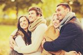 holidays, vacation, happy people concept - group of friends or couples having fun in autumn park