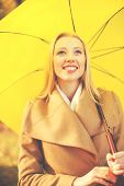 holidays, seasons, travel, tourism, happy people concept - smiling woman with yellow umbrella in the