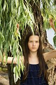 Portrait Of Teen Girl Standing Under The Branches Of Aspen And Move Them Hands