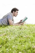 Side view of man reading book while lying on grass against clear sky