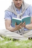 Low section of young man reading book on grass