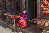 An Unidentified Little Girl Sitting That Sells Products Of Pottery In A Stall On December 2, 2013 In