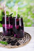 Tasty cool blackberry lemonade with ice on wooden table, on nature background