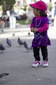 Sucre, Bolivia - January 17, 2012: A Girl Plays Feeding The Pigeons In The Main Square. January 17,