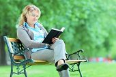 Mature woman reading a book in park seated on a bench