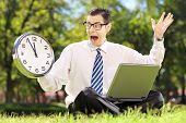 Young angry businessperson with computer sitting on grass and looking at clock in a parK