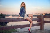 Outdoors portrait of romantic fashion young woman with long legs and hair in summer casual clothes s