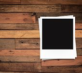 blank photo frame on wood background and free space on the left position