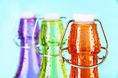 Colorful bottles on light blue background