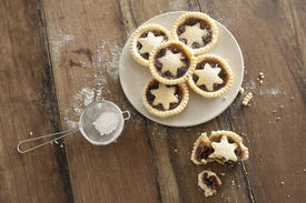 stock photo of icing  - Overhead view of a plate of decorative freshly baked Christmas mince pies with pastry stars alongside a half eaten pie and strainer with icing sugar to dust the top - JPG