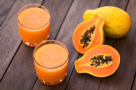 image of papaya fruit  - Two glasses of freshly prepared papaya juice with papaya fruits on the side  - JPG