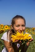 Young Woman With Sunflower In Field