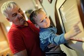 Grandfather And Grandson Using Touch Screen