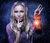 Closeup portrait of cute blond girl with red glowing lantern in hand showing not make a noise, dark starry night, Christmas eve concept