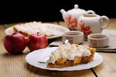 Piece Of Cake Decorated With Whipped Cream With Teaware And Apples Side View