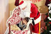 Santa Claus giving  present to sleeping little cute girl Christmas tree at home