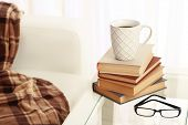 Tabletop with pile of books, cup and glasses near the sofa on light background