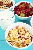 Various sweet cereals and berries in ceramic bowls and glass with milk on color wooden background