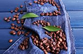 Green petals with coffee beans on blue wooden background with jeans material