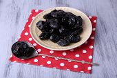 Plate of prunes on polka-dot napkin with spoon on color wooden background