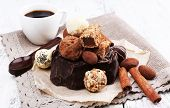 Pile of chunk of chocolate and truffles with cinnamon stick on crumbled paper, grey material and wooden background