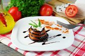 Eggplant salad with tomatoes and feta cheese on plate, on napkin,  on wooden background