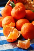 Fresh ripe mandarins on wicker basket, on napkin, on wooden background