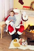 Santa Claus holding little cute girl near  fireplace and Christmas tree at home