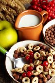 Various sweet cereals in ceramic bowls, fruits and jug with milk on napkin, on color wooden background