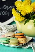 Yellow flowers in decorative teapot and tasty macaroons on wooden background