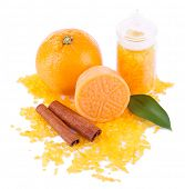 Bottle of bath salt with fresh orange, bar of soap and cinnamon isolated on white