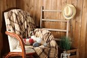 Rocking chair with plaid and yarn for knitting near wooden wall